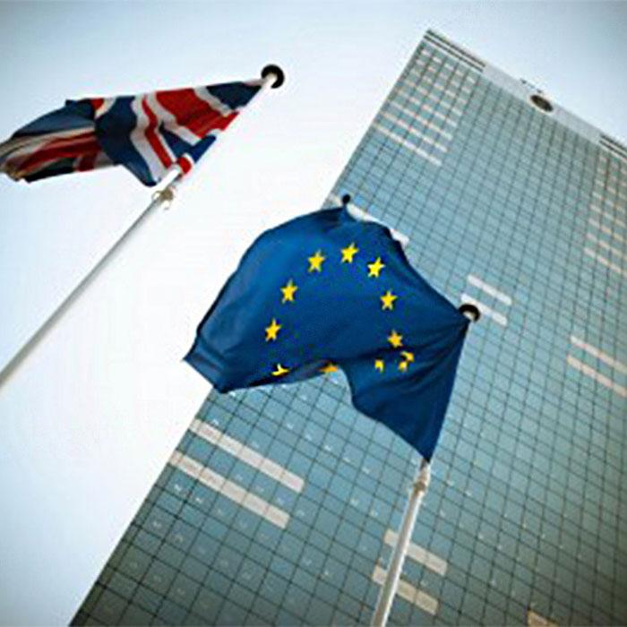 Flagge von England und die Flagge der Europäischen Union vor einem hohen Gebäude, symbolisiert den Brexit
