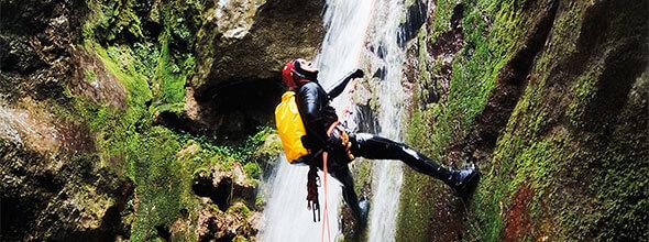 Person mit Kletterausrüstung, die an einer Wand, neben einem Wasserfall, mit einem Kletterseil hochklettert