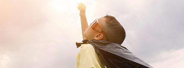 Junge, mit Umhang und Sonnenfinsternisbrille, der nach oben in die Sonne schaut und zeigt