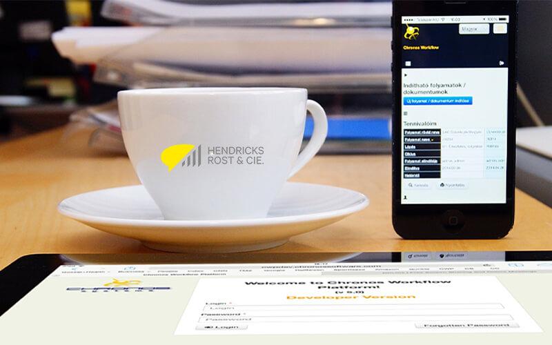 Kaffeetasse mit Untertasse auf dem Tisch, rechts daneben ein entsperrtes Handy und davor liegend ein entsperrtes Tablet