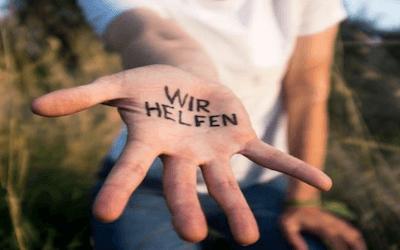 """Ausgestreckte Handinnenseite beschriftet mit den Worten """"Wir helfen"""""""